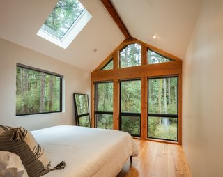 The cabin bedrooms feature skylights above the bed so that guests can watch the stars and tree canopy as they fall asleep and wake up. The bedrooms also have large floor-to-ceiling glazed doors that lead to a small timber deck with a built-in wood-fired cedar hot tub.