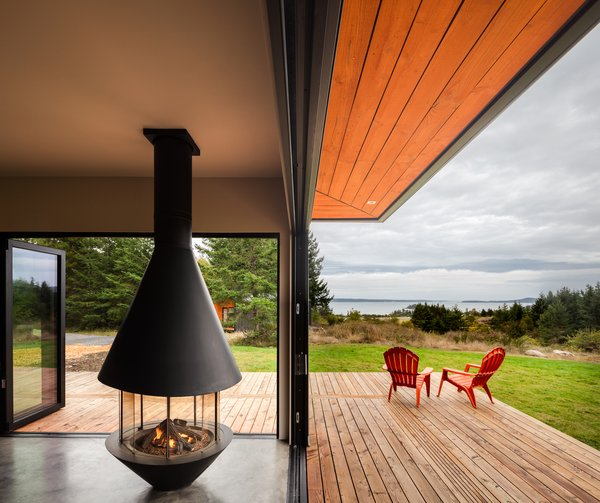 """We wanted to tie the living room together with a freestanding midcentury-style fireplace, which was a design collaboration between our team and Malm Fireplaces"" says designer Taylor Bode. ""When all of the bi-fold doors are open, you can sit in a circle around the fireplace both indoors and outdoors. It's an integral part of the design that brings warmth and light to the corner of the house."""