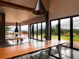 The communal dining table in the main house was custom-made by a local woodworker and island timber mill owner, Joe Romano, in collaboration with WindowCraft. Raw metal supports for the table were fabricated by Salish Metalworks on Orcas Island, a sister island to San Juan.