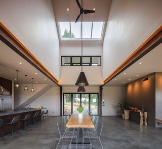"""Above the dining room there is an atrium with 28-foot vaulted ceiling and skylights. While the steel """"moment frame"""" structure was initially designed to be entirely framed in wood, the span required a switch to steel, which was left exposed as a design feature to create a """"wow"""" moment upon entry."""