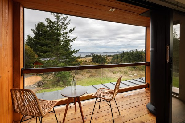 The deck adjacent to the master bedroom in the main house has views over the ocean. The chimney flue from the ground floor fireplace cuts through the corner of the deck, making the semioutdoor space useable even in cold weather.