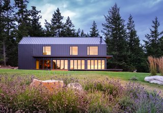 """The clients—Dr. Merriss Waters, a veterinarian, and Dr. Andrew Fleming, a clinical child psychologist—had a lifelong dream to live in a pristine, pastoral setting in the Pacific Northwest. """"They live an active lifestyle and enjoy exploring the islands,"""" says architect Taylor Bode. """"Their hobbies include mountain biking, trail running, farming, and cooking for friends and family.""""  In addition to an event space in an existing barn and cabin rentals, Saltwater Farm is home to productive gardens and a variety of animals."""