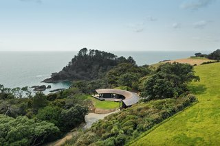 """It was essential that the home felt nestled into the landscape, rather than perched on the edge of the dramatic clifftop site. """"My client had commissioned a house design that was rejected by members of his family—the formidable force that is his sisters,"""" says architect Belinda George. """"They felt the site deserved a more considered approach. As I had worked for Tom before on more urban projects, he asked me to design a bach for him and his family. He wanted it to feel relaxed and connected to the land."""""""