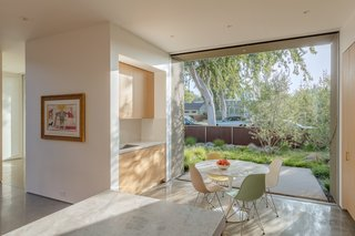 "Pocketed sliding doors connect the breakfast nook to the front yard, which is screened from passersby with olive trees. ""Enjoying the early morning light that enters the breakfast nook is a great way to wake up while having a cup of coffee,"" says Joseph."