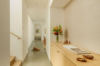 Custom millwork units are strategically located in every space—including hallways—to provide ample storage for the growing family.