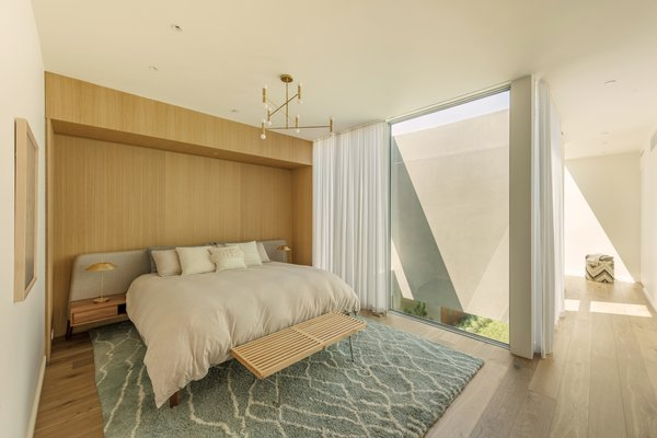 When the blinds are open, the glazed walls in the master bedroom frame the sculptural pine tree in the atrium below. A white oak feature wall references the bespoke joinery throughout the home.