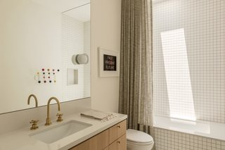 The guest bathroom features Silver Ice quartzite surfaces, which match those in the kitchen. A decorative shower curtain, rather than a glass barrier, softens the space and adds texture.