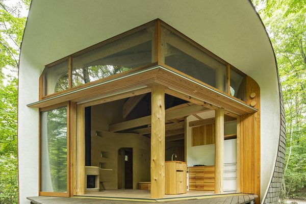 The window and door frames are mainly crafted from cedar. They sit within the curved shell, which has deep eaves that protect the interior from the sun and reference traditional Japanese architecture.