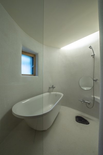The bathroom is located on the ground floor, and it features white cement walls. A rough-hewn stone covers the floor drain, again referencing the surrounding forest and nearby waterway.