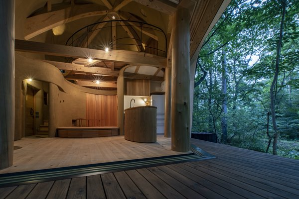 The large wooden deck, crafted from Japanese red pine and chestnut timber, extends the living space into the forest. A view from the deck shows the curved interior and the roof structure.