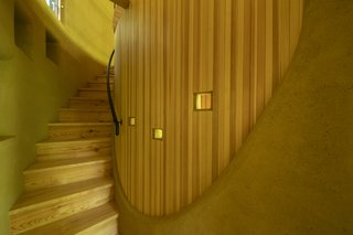 A timber stair curves up behind the living and sleeping platform on the ground floor. The curved details of the timber and earth walls echo the organic form of the building.
