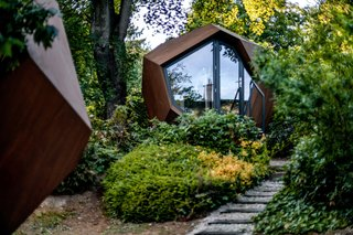 The design team wanted to create a cabin that felt connected to nature, both in the exterior and interior. The organic form sits easily in the landscape, while large windows invite garden views inside.