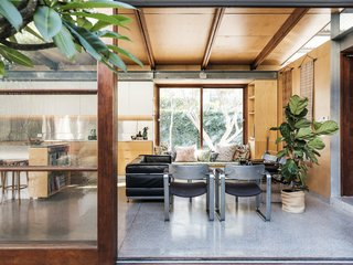 The newly built living room opens to the courtyard and connects the front and rear wings of the home. The floor is exposed concrete with a sustainable fly-ash mix.