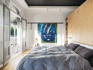 The master bedroom features an original pressed-metal ceiling that was restored. It opens out onto a large balcony, which is typical of Sydney terrace houses. A bespoke hoop-pine plywood joinery unit creates ample storage and offers space for a separate dressing room behind the bed.