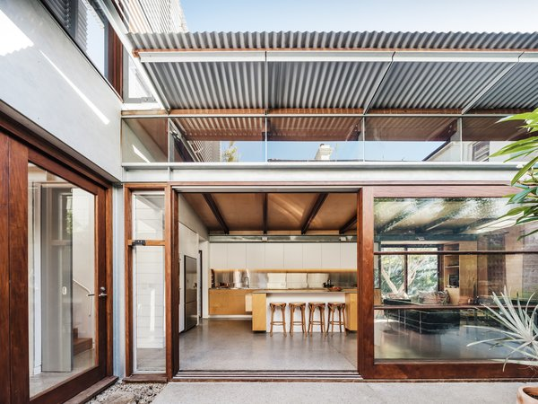 The open galley kitchen flows seamlessly into the living room. The joinery is hoop-pine plywood, which echoes the materiality of the ceiling and walls.