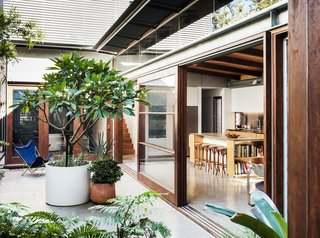 "Central to the courtyard is a frangipani tree—""the house's own axis mundi of sorts,"" says Joe. All the living areas, including an open galley kitchen, are on the ground floor and seamlessly open to one another. The garage—which is used as a multifunctional space rather than for parking—is also directly connected to the courtyard via a glazed opening, and the two areas can be configured as a large indoor/outdoor space for gatherings."