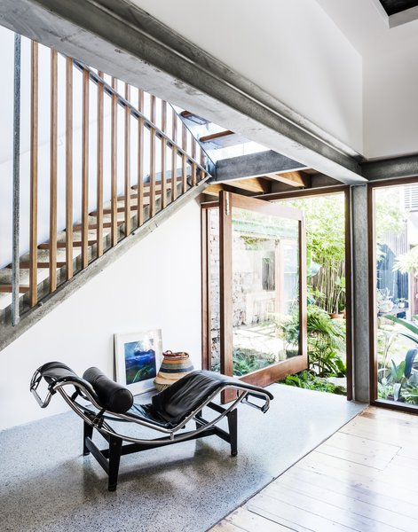 "The design intention was to keep the stair as simple and understated as possible. It's crafted from plate steel stringers and blackbutt timber treads. A central steel truss ""hovers"" between the stair flights and includes blackbutt uprights. A pivoting door beneath the stair opens out to the courtyard."
