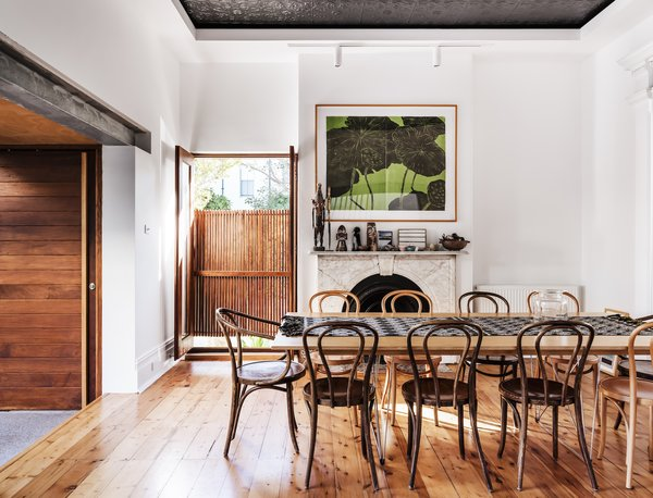 """The dining room, which features an original pressed-metal ceiling detail and fireplace, has a large window that opens directly to the sidewalk. The step down from the dining room to the living room represents the junction between the original terrace and the newly built addition. The exposed steel beam running above this junction is also new. """"In opening up the house to the courtyard, we had to remove two walls,"""" says Joe. """"The steel beams and column support the upper floor of the original house in this area."""""""