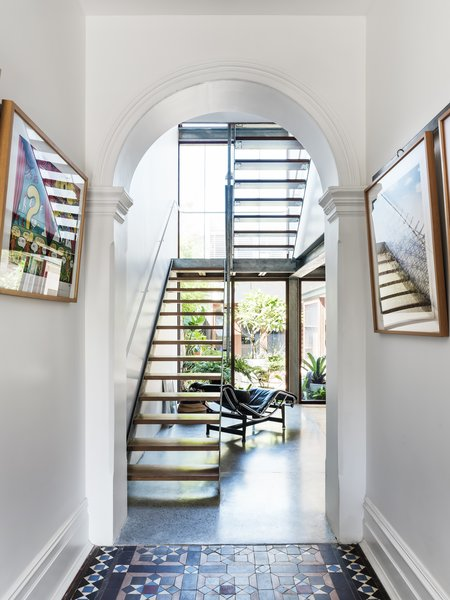 The archway at the end of the entrance hall was opened up to reflect the original floor plan of the terrace, and now leads directly to the stairs and the living/dining area.