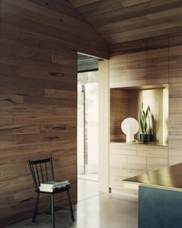 Timber has been used for both internal and external cladding, joinery, furniture, and door handles throughout the home. The entry nook features built-in display storage with brass detailing, which is echoed in the kitchen counter.