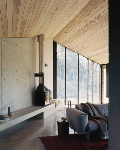 """At the far end of the """"living shed"""" is a fireplace and concrete bench, which offers a contemplative space for reading and watching the bushland through the windows."""