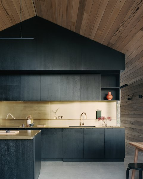 "The kitchen is located in a bespoke timber joinery unit that divides the ""living shed."" The timber has been stained black to contrast with the surrounding timber cladding, and brass counters and backsplashes echo the use of brass details throughout the interior. ""Brass was a very special material—used sparingly—that has come to be a hallmark of the project,"" says architect Ben Shields."