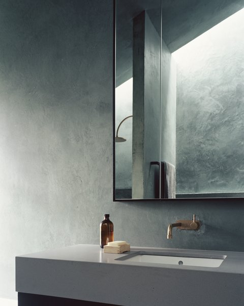 """The bathroom vanity's concrete counter echoes the use of concrete in the living space. """"We tend to try to use as few materials as possible when we design at DREAMER,"""" says Shields. """"The calmness that comes with a pared-back approach is something we value in spaces."""""""