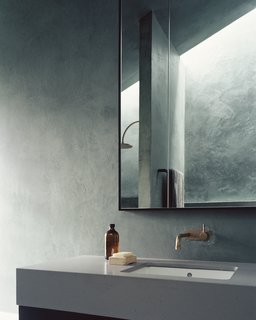 "The bathroom vanity's concrete counter echoes the use of concrete in the living space. ""We tend to try to use as few materials as possible when we design at DREAMER,"" says Shields. ""The calmness that comes with a pared-back approach is something we value in spaces."""