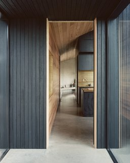 """""""We wanted the entry to give a sense of the house without giving too much away—and to draw the eye to the glazed entry gallery and the beach and hills beyond,"""" says architect Ben Shields. """"We also wanted to start to materially tell the story of the house."""""""