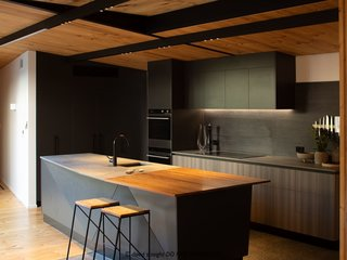 "The kitchen island features a top made from concrete and rimu, a native New Zealand timber. As rimu is no longer harvested, the piece was pulled from a swamp and is potentially around 1,000 years old. The split between the concrete and timber reflects the split between the flooring materials. ""The faceted form of the island ties into our concept and links to the fractured forms on the exterior of the house,"" says Craig."