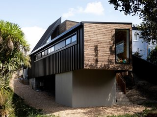 """There is a play between really earthy, natural materials—which are seen in some of the cladding, tiles, and concrete work—and a very sleek, black metal aesthetic. """"I have a lot of experience in commercial architecture, so I'm not scared of using more commercial, industrial materials on a residential building,"""" says Craig."""