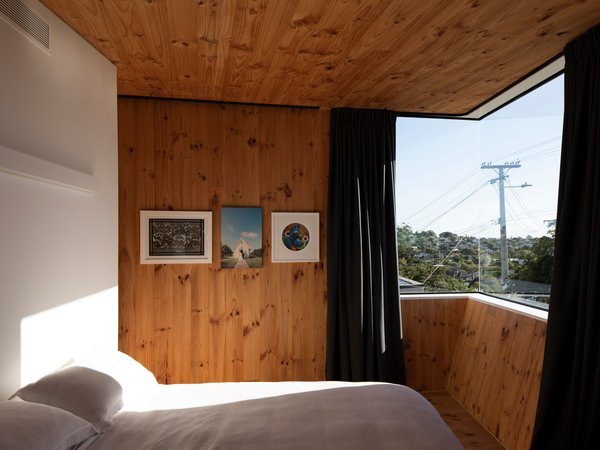 The master bedroom is on the second story. It's a private space for Craig and his wife that also incorporates a study, an en suite bath, and a walk-in wardrobe. Timber cladding gives the home's interior a cozy feel.