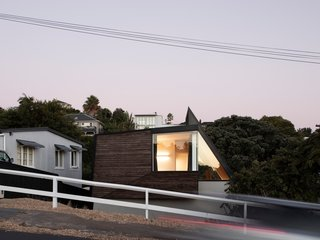 The house fronts the street with the large top story and a sharply angled roof that defines the staircase, creating a striking form—especially at night, when it is lit up from within.