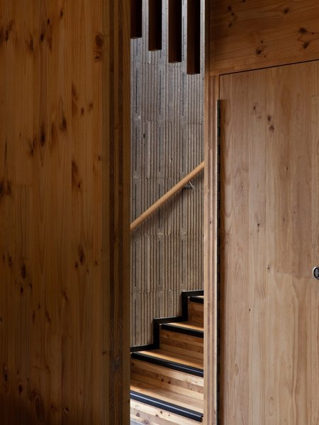 """The wall beside the stair is made from off-form concrete, which is insulated on the outside. Polystyrene molds created a textured pattern on the concrete wall that celebrates the honesty of the home's materials and construction. """"It looks very gridded and regimented, but every part of the grid is unique,"""" says Craig."""