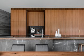 The kitchen counters are Pietra Gray marble, which complements the refinement of the spotted gum timber joinery.