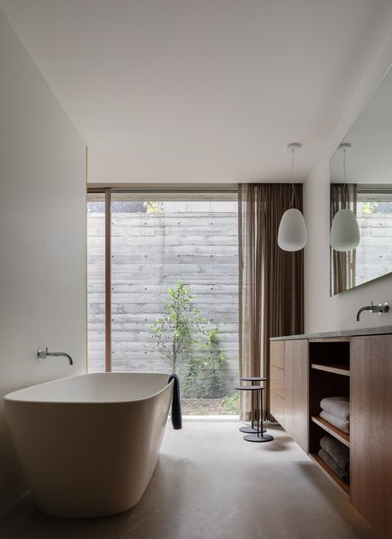 The master bathroom is located next to the bedroom and also opens up to the sunken courtyard.