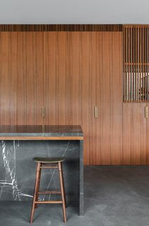 The spotted gum joinery in the kitchen dissolves into the sliding screen that divides the library/study from the living area. Brass details, such as the handles and the seat of the stool, add warmth to the material palette.