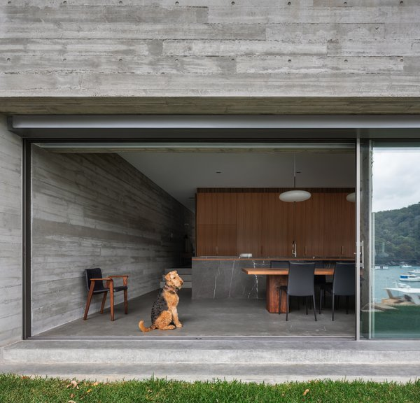 The dining and kitchen space opens up directly to an expanse of grass that leads to the water's edge.