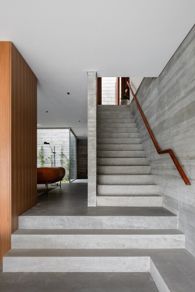 The concrete stairwell leads from the ground floor up to the front door and a sliding partition that opens to two more bedrooms and another living space with a kitchenette. The library/study and living room spaces are separated by several stairs to create connected yet separate living spaces.