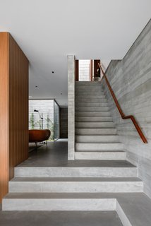 混凝土楼梯间从一楼到前门打开到两个卧室和一个小厨房的另一个生活空间滑动分区的线索。图书馆/书房和客厅的空间是由几个楼梯隔开来创建连接但独立的生活空间。