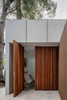 The front door is crafted from solid spotted gum hardwood, which echoes the joinery used in the interior.
