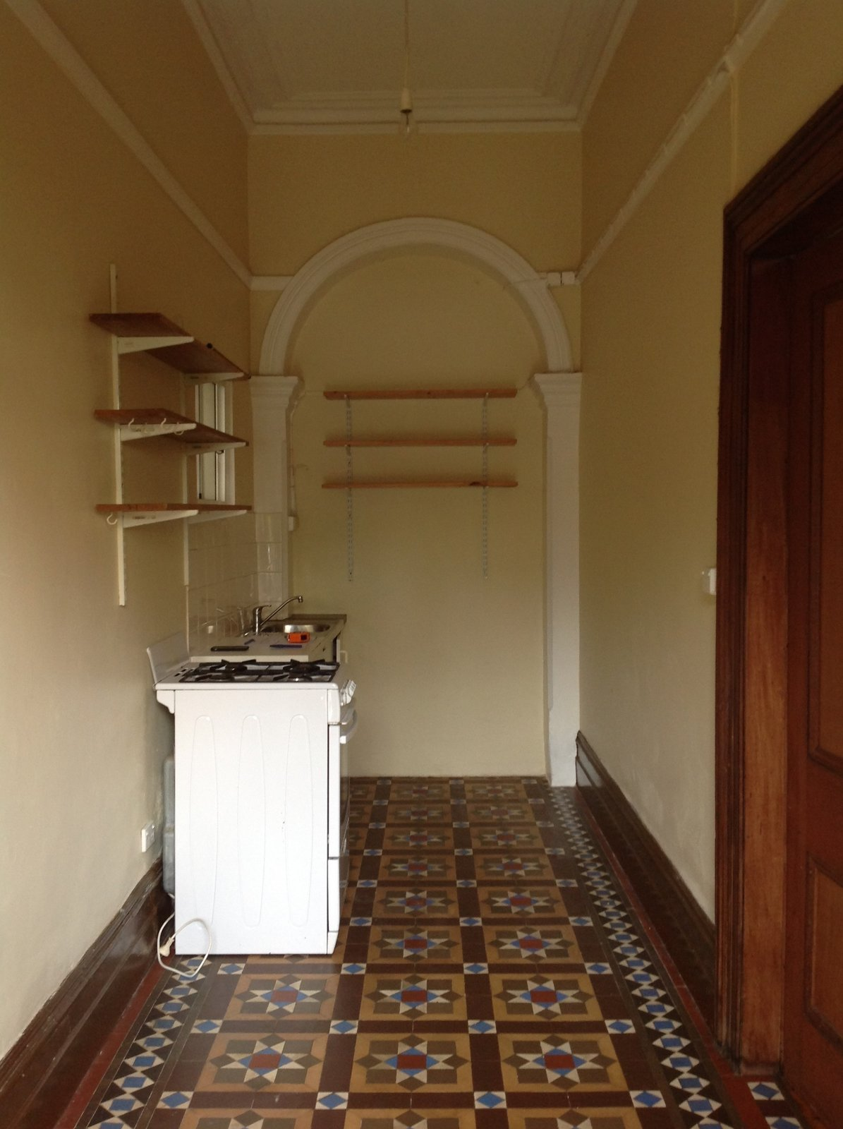 Before: The boarding house arrangement meant there were kitchens and bathrooms everywhere—even in the entrance hallway, which had also been closed in.  Photo 8 of 37 in Before & After: A Blighted Boarding House in Sydney Is Now an Adaptable Courtyard Home
