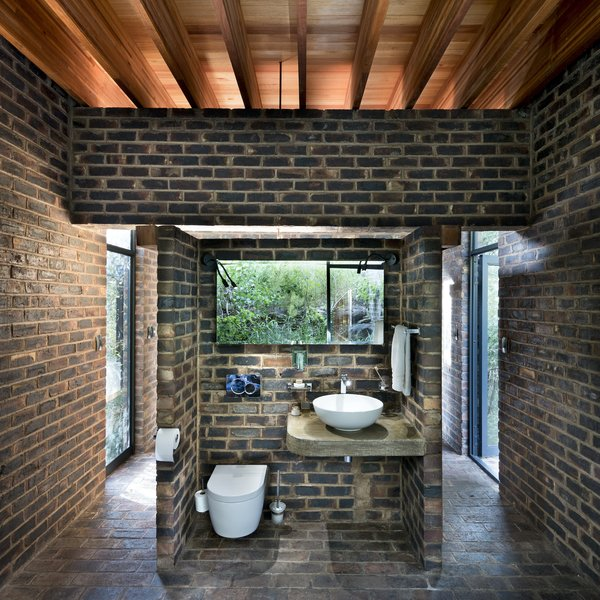 The bathroom has views to the bushland on the cliff. The space is entirely open, with privacy afforded by the remote location and dense vegetation.