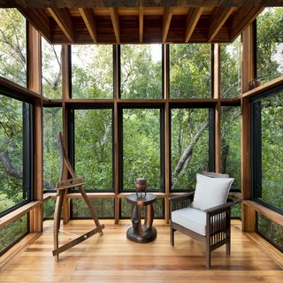 """The bedroom/living space is enclosed by large glass windows framing the treescape. """"I think one of the most successful experiential aspects of a building is how intimately involved it is with the site,"""" says architect Ant Vervoort. """"An expensive view has the effect of divorcing one from the site. In House of the Tall Chimneys, the views are very close and intimate, which makes you part of the site."""" The timber used throughout is Eucalyptus saligna, which is native to Australia and sustainably grown and harvested in South Africa."""