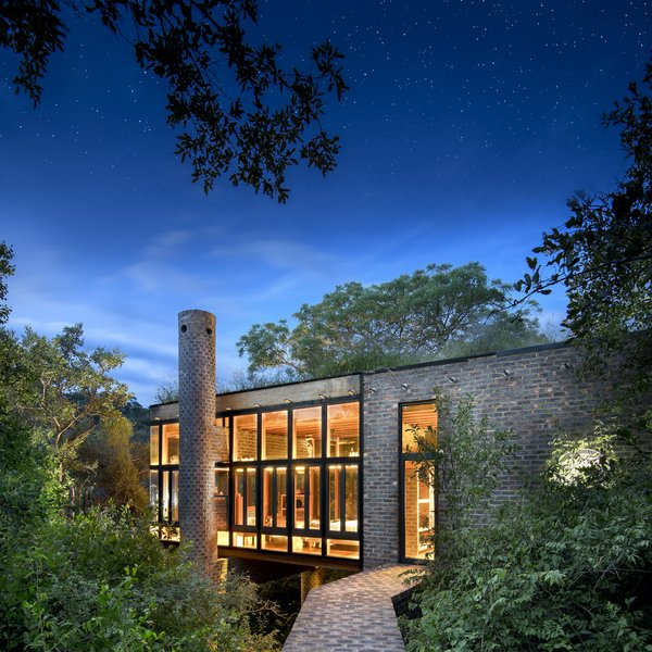 "A brick path leads through the forest to the entrance of House of the Tall Chimneys. ""Bricks are a really cost effective way of creating space,"" says architect Ant Vervoort. ""Over and above that, when used correctly, bricks create complex patterns that I don't think it's possible to mimic using other materials."""