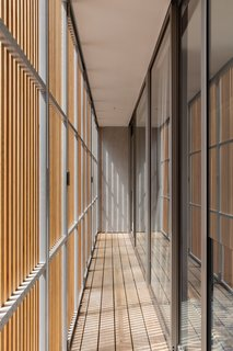 A narrow, screened timber deck runs in front of the upper-floor living space and guest bedrooms. Privacy is provided by a spotted gum timber screen.