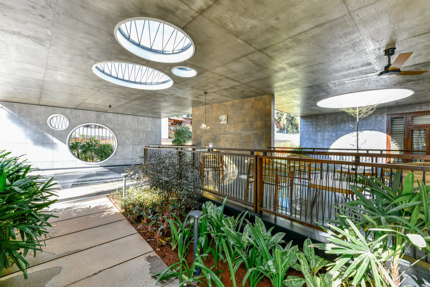 Circular Skylights Let the Landscape Grow Through This Concrete Home in India