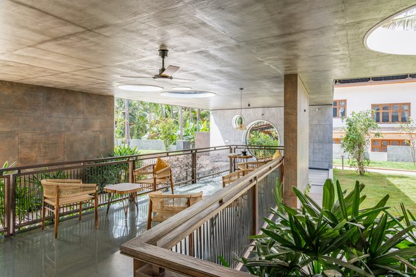 "The ""sit-out"" is located in a grassed courtyard area. The concrete structure is softened by a warm timber balustrade, rattan furniture, and glass pendant lighting."