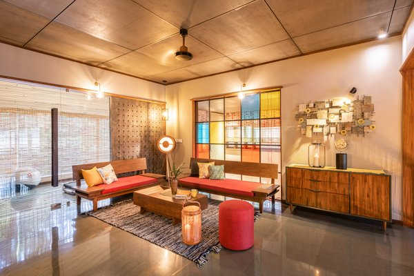"""The private family sitting room on the first floor overlooks the atrium above the dining space through a colored glass screen that matches the one on the ground floor. Bamboo screens provide a """"buffer"""" against harsh sunlight."""