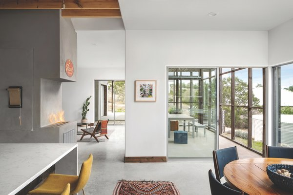 """My mom really wanted a fireplace, even though they don't make sense in Texas and generally are an energy drain—and she wanted it to somehow serve the living, kitchen, and dining spaces,"" says architect Ryan Bollom. ""So, we wound up using a clean-burning fireplace insert designed to fit in the transition that distinguishes each of the spaces without making them feel like different rooms."""